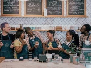 6 staff members laughing behind the counter
