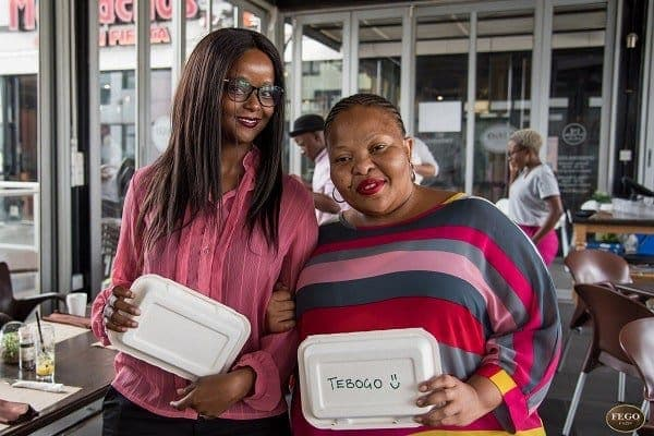 Two women holding GREEN HOME takeaway containers, smiling at the camera