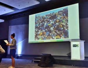 Cat speaking in front of a large slide showing trash on a landfill