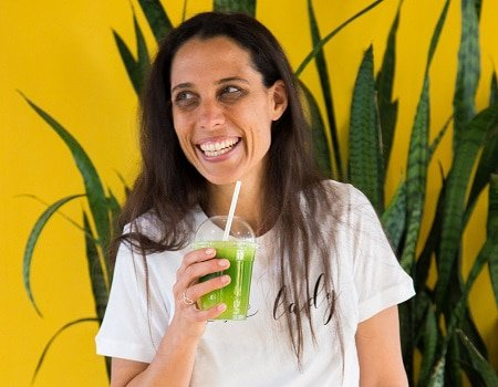 Catherine Morris smiling and holding a smoothie cup with paper straw and green juice