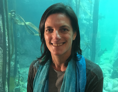 Hayley McLellan standing in front of a tank at the Two Oceans Aquarium