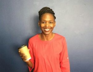 Photo of a smiling Phindi Dlamini, standing in front of a blue wall holding a Kraft Hot Cup