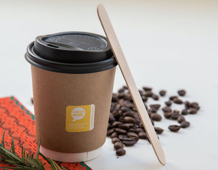 A GREEN HOME Hot Cup with the lid on. A wooden stirrer is leaning against the cup
