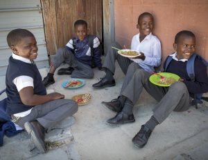 Four boys in uniform eating a meal outside