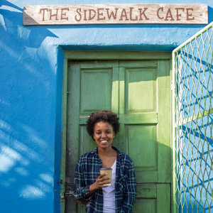Woman holding biodegradable coffee cup against bright blue wall and under a 'Sidewalk Cafe' sign