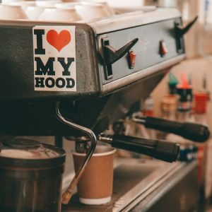 Close up of coffee machine with biodegradable coffee cup & 'I heart my hood' sticker