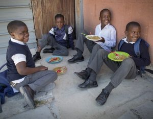 Four boys in school uniform enjoying a meal