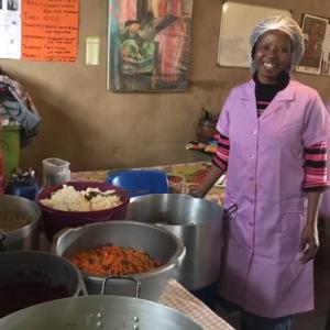 A volunteer at Yiza Ekhaya standing with big pots of food