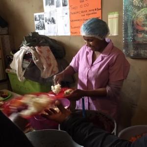 A volunteer at Yiza Ekhaya dishing up food