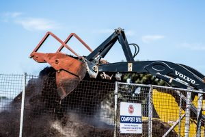 A forklift machine turning a large compost pile