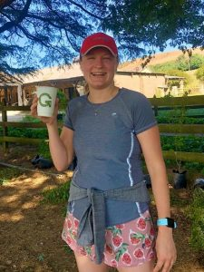 A woman in sports gear holding a Green Home cup and smiling