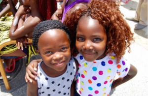 Two of the Yiza Ekhaya girls standing outside in the sun and smiling at the camera