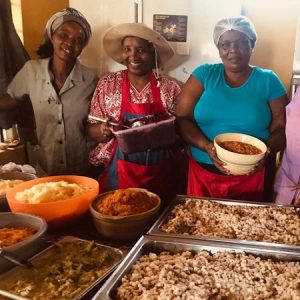 Mama Mickey and some of her volunteers with big trays of cooked food