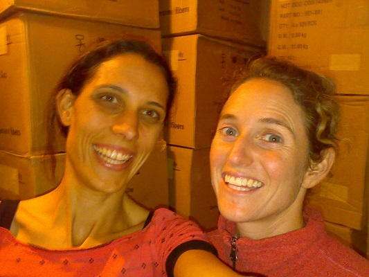 Catherine with a friend, both smiling happily in front of boxes of stock