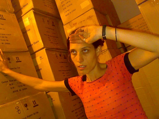 Catherine after offloading her first container into her lounge, leaning against boxes after working hard