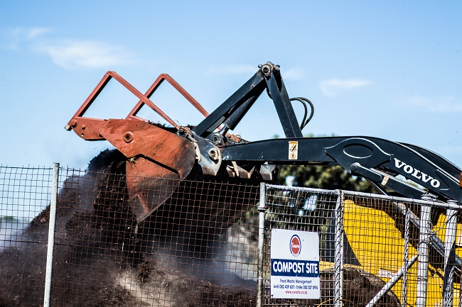 A forklift turning compost at a composting site