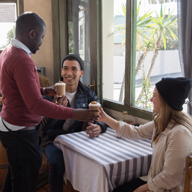 a women and man smiling as theyre given green home hot cups from a man in a cafe