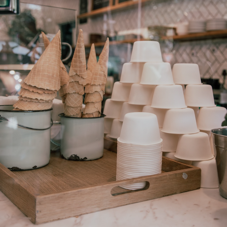A stack of GREEN HOME bagasse bowls on a counter next to ice cream cones
